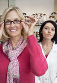Portrait of a happy woman trying glasses with optician in background — Stock Photo
