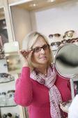 Senior donna cercando occhiali guardando nello specchio di mano nell'archivio — Foto Stock