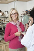 Portrait of senior woman wearing glasses while optician holding mirror — Stock Photo