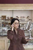 Beautiful mid adult female customer trying on glasses while looking into mirror — Stock Photo