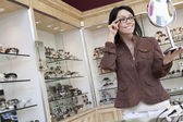 Happy mid adult customer trying on glasses while looking into mirror — Stock Photo