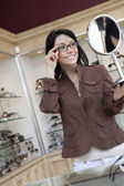 Happy mid adult woman trying on glasses while looking into hand mirror — Stock Photo