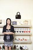Retrato de una mujer adulta media de pie con los brazos cruzados en zapatería — Foto de Stock