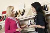 Happy mature salesperson with mid adult customer in shoe store — Stock Photo