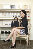 Portrait of a mid adult woman showing designer handbag in footwear store — Stock Photo