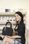 Portrait of a happy mid adult woman showing designer purse in shoe store — Stock Photo
