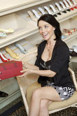 Cheerful mid adult woman with footwear box in shoe store — Stok fotoğraf
