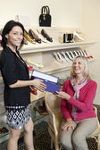 Portrait of a mid adult salesperson giving footwear box to mature female customer in shoe store — Stock Photo