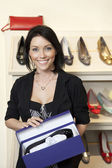 Portrait of a happy mid adult woman with footwear box in shoe store — Stock Photo