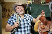 Happy mature cowboy with saddle and rope in feed store — Stockfoto