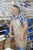 Happy mature man pushing cart in feed store — Stock Photo