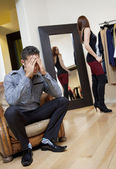 Worried young man sitting on armchair with woman in background trying on clothes — Stock Photo