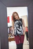 Mirror reflection of a young woman trying on clothes in fashion boutique — Stockfoto