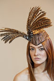Portrait of a young woman wearing feathered headdress on colored background — Stock Photo