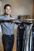 Portrait of a happy young male standing by clothes rack in fashion store — Stock Photo