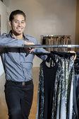 Porträt einer glücklich junge männliche beisteht kleidung rack in mode speichern — Stockfoto