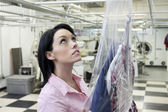 Beautiful woman looking up in laundry — Stock Photo