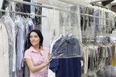 Glad mitten av vuxen kvinna tittar bort samtidigt sätta kläder i plast — Stockfoto