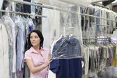 Happy mid adult woman looking away while putting clothes in plastic — Stock Photo