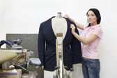 Portrait of a mid adult woman dressing mannequin — Stock Photo