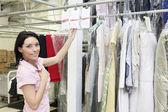 Portret połowie dorosła kobieta stojąc przez wieszaka na ubrania — Zdjęcie stockowe