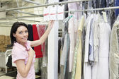 Porträtt av en mitten av vuxen kvinna som står vid kläder rack — Stockfoto