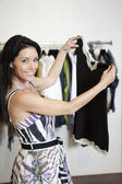 Portrait of a beautiful mid adult woman standing with top in fashion shop — Stock Photo