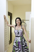 Portrait of a mid adult woman standing at doorway of dressing room in fashion boutique — Stock Photo