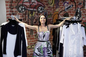 Portrait of a happy mid adult woman standing by clothes rack with graffiti in background — Stock Photo