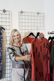 Portrait of a happy senior woman browsing in fashion boutique — Stock Photo