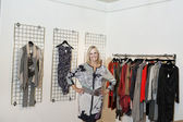 Portrait of a happy senior woman standing with hands on hips in fashion boutique — Stock Photo