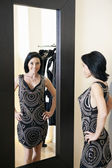 Happy mid adult woman wearing a stylish dress standing in front of mirror with hands on hips in boutique — Stock Photo