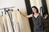 Portrait of a beautiful mid adult woman selecting dress from rack in fashion boutique — Stock Photo