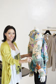 Portrait of a beautiful mid adult woman standing by mannequin in fashion shop — Stock Photo