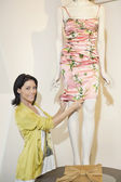 Portrait of a beautiful mid adult woman adjusting dress on mannequin in fashion boutique — Stock Photo