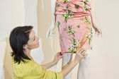 Beautiful mid adult woman adjusting dress on mannequin in fashion store — Stock Photo