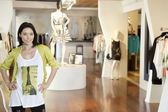 Portrait of a happy mid adult woman standing with hands on hips in fashion clothing store — Foto de Stock