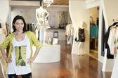 Portret van een gelukkig medio volwassen vrouw permanent met handen op de heupen in mode kledingwinkel — Stockfoto