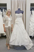 Portrait of a happy woman standing by elegant bridal dress in boutique — Stock Photo