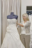 Senior female owner adjusting wedding dress on mannequin in bridal store — Stock Photo