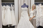 Portrait of a happy senior female adjusting wedding dress on mannequin in bridal store — Stock Photo