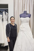 Portrait of a mature employee standing by elegant wedding dress in bridal store — Stock Photo