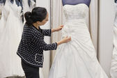 Side view of mature woman adjusting bridal dress in boutique — Stock Photo