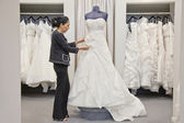 Side view of a mature employee adjusting elegant wedding dress in bridal store — Stock Photo