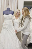 Happy mother and daughter looking at beautiful wedding dress in bridal store — Stock Photo