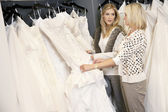 Mother and daughter looking at each other while selecting wedding gown in bridal store — Stock Photo