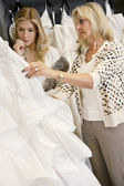 Mother selecting wedding dress for young daughter in bridal store — Stock Photo