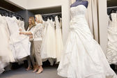 Happy mother and daughter shopping together for wedding gown in boutique — Stock Photo