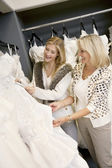 Cheerful young daughter with senior mother selecting wedding dress in bridal boutique — Stock Photo