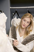 Beautiful young woman looking at price tag of wedding dress in bridal store — Stock Photo